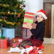 Young girl shaking christmas gift — Stock Photo
