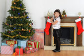 Surprised little girl with christmas stocking — Stock fotografie