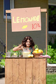 Young girl making lemonade at her stand — Stock Photo