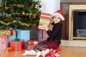 Young girl shaking christmas gift — Foto de Stock