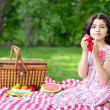 Girl at picnic using red napkin — Stockfoto
