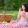 Little girl eating apple at picnic — Stock Photo