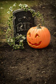Pumpkin and tombstone — Stock Photo