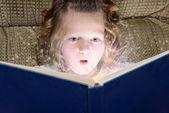 Little girl enjoying magic of reading — Stock Photo