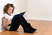 Young girl leaning on wall reading book — Stockfoto