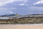 Dunstanburgh castle from beach — Stock Photo