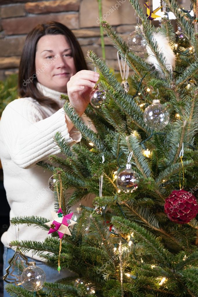 Young woman is decorating Christmas tree at home  Stock Photo #13858718