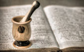 Mortar and pestle on pharmacy book — Stock Photo