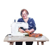 Elderly woman sews with her sewing machine. Isolated on white. — Stock Photo