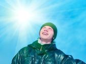 Smiling teenager on blue sky background — Stock Photo