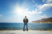 Man stands on a background of sea and sun — Stock Photo