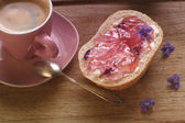 A bread roll with violet jelly   — Stock Photo