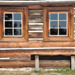 Wooden cottage facade with windows and bench — Stock Photo #12776253