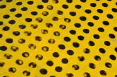 Yellow metal sufrace withe holes — Stock Photo