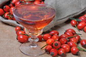 Rosehip fruit and alcoholic liquor — Stock Photo