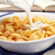 Pouring milk over cornflakes — Stock Photo