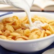 Pouring milk over cornflakes — Stock Photo #12083135