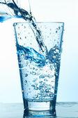 Colocar água no copo com bolhas. — Foto Stock