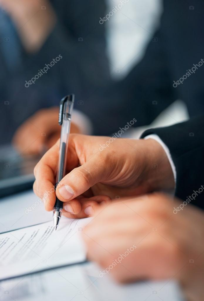 Close-up picture of businessman's hand writing in the document — Stock Photo #12081865