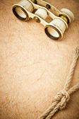Old binoculars on vintage paper background — Stock Photo