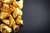 Gold nuggets on a black background. closeup — Stock Photo