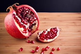 Ripe pomegranate fruit on wooden table — Stock Photo