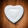 Heart form white plate on wood background — Stock Photo