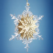Glass snowflake on blue background — Stock Photo