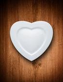 Piastra di cuore forma bianca su sfondo legno — Foto Stock