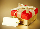 Christmas gift box on gold background — Stock Photo