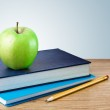 Book, notebook with apples and pencil on table — Stock Photo