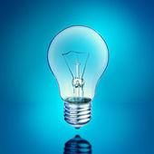 Light bulb on blue background — Stock Photo