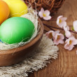 Easter eggs and branch with flowers on wooden — Stock Photo