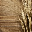 Wheat on wood background — Stock Photo #22157355