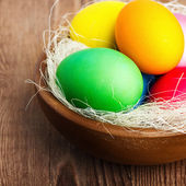 Easter basket with easter eggs on wooden background — Stock Photo