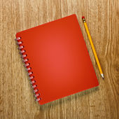 Pencils and notebook on a wooden background — Stock Photo