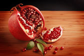 Delicious pomegranate with seeds on wooden table — Stock Photo