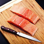 Salmon fillet with knife on wood board — Stock Photo