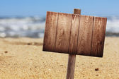 Wooden signboard on tropical beach — Stock Photo