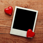 Photo frame and small red hearts — Stock Photo