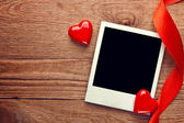 Blank instant photo and small red hearts with ribbon — Stockfoto