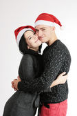 Loving young happy couple in christmas hats — Stock Photo