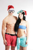 Young attractive fit couple in christmas hats — Stock Photo
