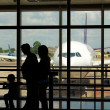 A family at an airport terminal with aeroplane in the background — Stock Photo