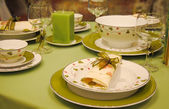 An elegant dining setting with green tableware — Stock Photo