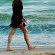 Stock Photo: A woman walking barefeet on the beach