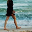 Stock Photo: Womwalking barefeet on beach