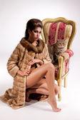 若い女性の毛皮のコートと肘掛け椅子の上の猫 — ストック写真