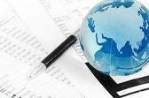 Glass globe and pen on finance — Stock Photo