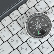 Computer keyboard and retro compass — Stock Photo